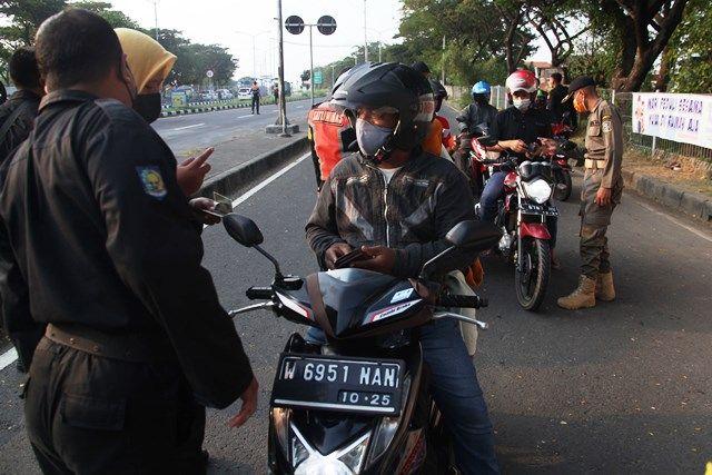 PENYEKATAN: Petugas memeriksa kelengkapan dokumen pengendara yang melintasi Jembatan Suramadu di Tambak Wedi, Surabaya, Senin (7/6).