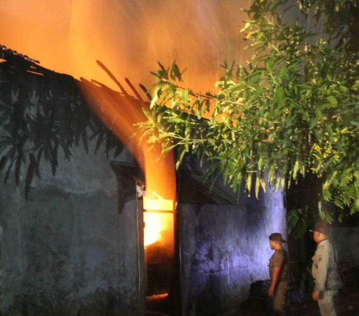 LUDES : Petugas berusaha memadamkan si jago merah yang telah melalap gudang milik H Khomsul.