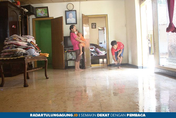 BERSIH-BERSIH: Sriyati dan Endah sedang membersihkan lumpur di dalam rumahnya setelah terjadi luapan air kemarin (30/11).