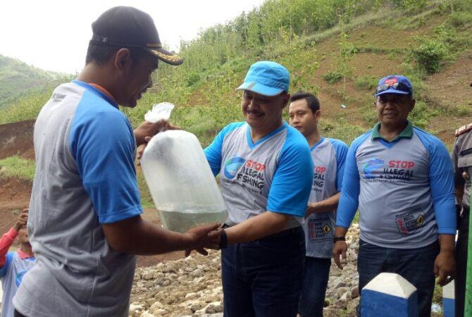PEDULI LINGKUNGAN : Kepala Dinas Perikanan Tulungagung Tatang Suhartono (topi biru) saat menyerahkan ikan kepada warga, Jumat (7/12).
