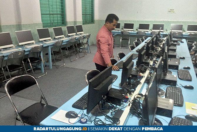 TERUS BERUSAHA MANDIRI: Seorang guru tengah menyiapkan sarpras guna menunjang ujian.