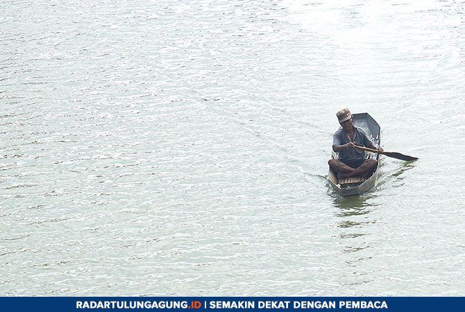 MASIH ADA: Seorang bapak tua sedang mendayung perahu di Sungai Parit Agung, Campurdarat.