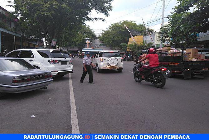 HATI-HATI DI JALAN: Seorang petugas parkir di area Jalan Dewi Sartika Trenggalek mengatur kendaraan yang masuk.