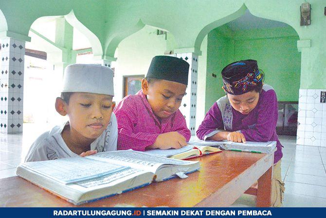 MENUNGGU: Sejumlah murid TPA Darussalam sedang belajar membaca Alquran sambil menunggu guru atau pengajar mereka datang, Kamis (7/2).