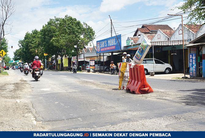 PICU KEMACETAN: Tong dan water barrier diletakkan di tengah jalan raya nasional di Desa Bolorejo, Kecamatan Kauman, untuk menandai jalan yang berlubang. Jalur ini menghubungkan Tulungagung dan Trenggalek.