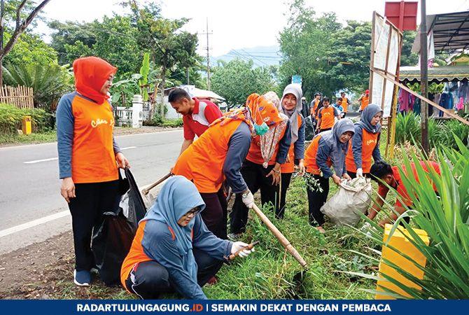 JAGA LINGKUNGAN: Warga Kecamatan Pogalan membersihkan area Puskesmas Pogalan.