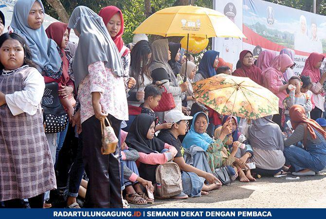 SABAR YA: Ratusan masyarakat Trenggalek rela berpanas-panasan di Pendapa Manggala Praja Nugraha, menunggu kehadiran Wagub Jatim Emil Elestianto Dardak.