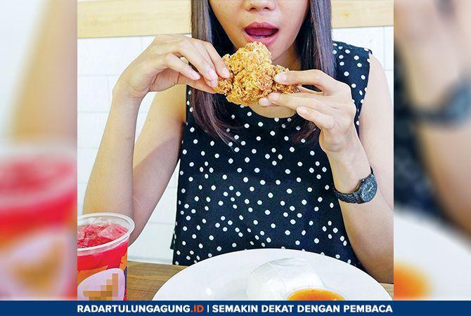 CEPAT SAJI : Seorang model, Fadila sedang memperagakan makan makanan yang termasuk junk food. Konsumsi junk food berlebihan bisa mengganggu kesehatan tubuh.