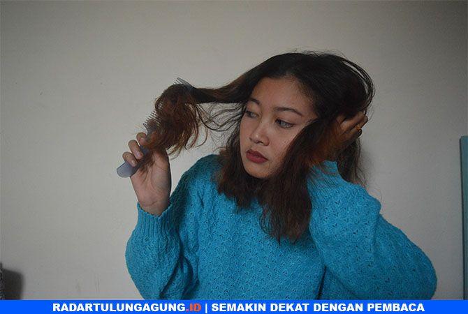 KERING: Rafika Erny Nabila saat menyisir rambutnya yang rontok. Terlalu sering hairstyling dapat membuat rambut kering.
