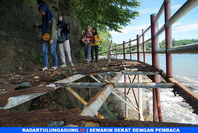 MENGKHAWATIRKAN: Pengunjung Pantai Popoh hendak melintasi jembatan penghubung yang pelatnya sudah rusak.