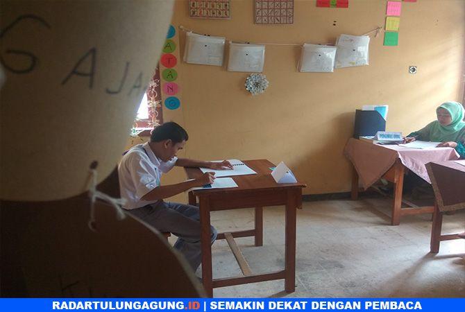 FOKUS : Fajar saat mengerjakan soal ujian nasional berbasis kertas (UNBK) dengan serius.