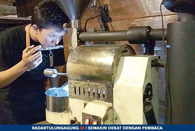 TELATEN: Hengky ketika meroasting biji kopi.