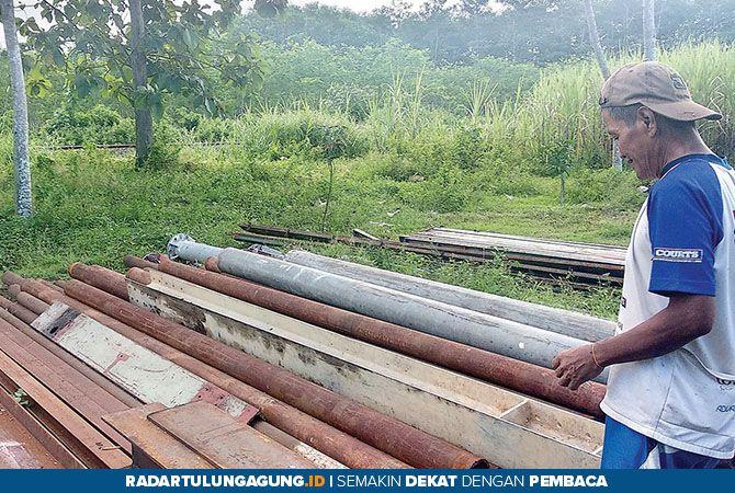 TETAP LAKU: Matrohwi dengan tumpukan besi tua yang menjadi tulang punggung bisnisnya.