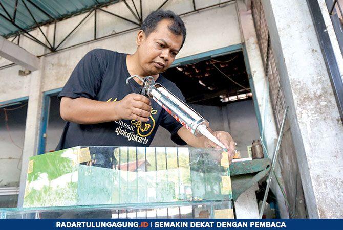 SANGAT BERBEDA : Priyo Pambudi sedang membuat aquarium pesanan pelanggannya yang dipastikan hemat daya.