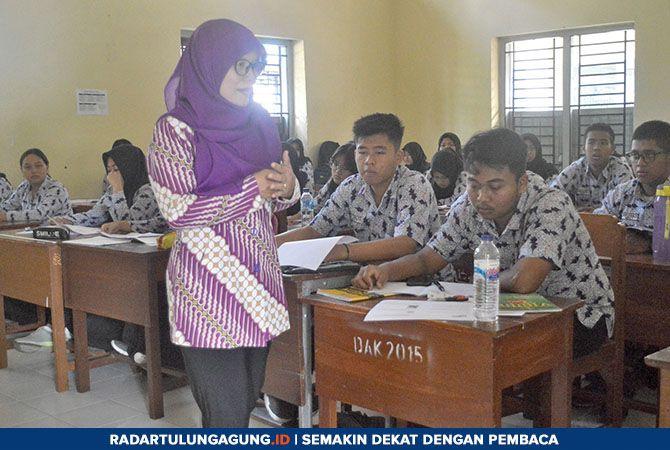 MASIH KURANG : Seorang guru mengajar di salah satu ruang kelas SMAN 1 Kedungwaru beberapa waktu lalu.