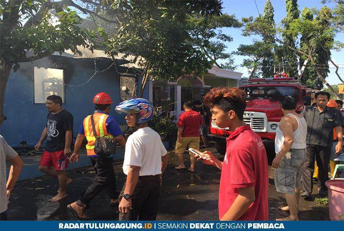 MENYEDIHKAN : Rumah korban terlihat hangus terbakar dan sejumlah warga berusaha memadamkan api.