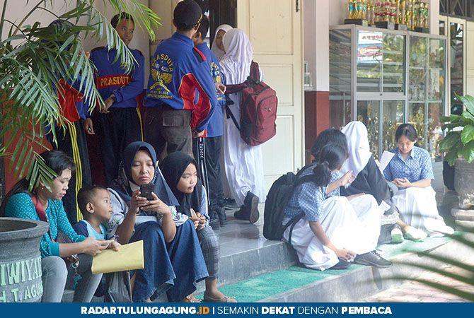 ANTRE: Calon siswa dan wali murid menunggu pembagian bukti pendaftaran PPDB online di SMPN 2 Tulungagung, kemarin (21/6).