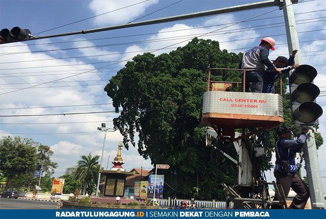 PEREMAJAAN: Petugas Dishub Kota Blitar memperbaiki lampu traffic light, Selasa (9/7).