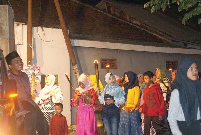 SUKA CITA: Sejumlah anak membawa oncor berkeliling menyusuri jalan desa di malam takbiran, Sabtu malam.