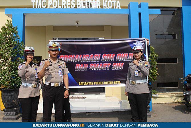 LEBIH CEPAT: KRI Satlantas Polres Blitar Kota Ipda Luhur Santoso bersama anggota polwan menunjukkan spanduk sosialisasi Smart SIM dan Registrasi SIM ONLINE.