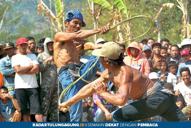 TIDAK TAKUT: Dua orang peserta saling melecutkan cemeti saat digelar kesenian tiban di lapangan Desa Ngulan Wetan, Kecamatan Pogalan, kemarin (13/10).