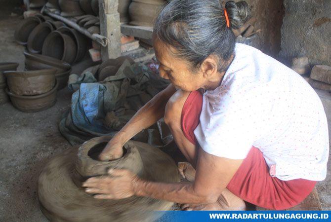 KOSENTRASI: Mbah Sumiati sedang membuat lambung kuali dengan batu dan tatap.