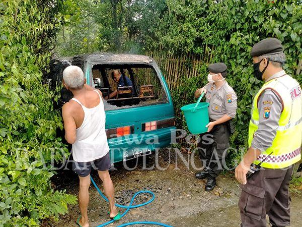 PROSES PEMADAMAN: Sejumlah petugas dan warga sedang memadamkan mobil yang terbakar di jalan desa masuk RT 08/RW 03, Dusun Kepanjen, Desa/Kecamatan Suruh, kemarin (18/5).