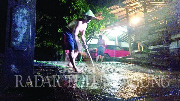 BERSIH-BERSIH LUMPUR: Salah seorang warga sedang membersihkan sisa-sisa lumpur akibat luapan sungai temon di Desa Ngares, Kecamatan Trenggalek, Senin (18/5) lalu.