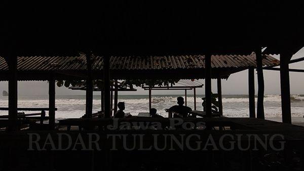 BERSANTAI: Beberapa warga tak panik di tengah banjir rob di Pantai Konang kemarin (26/5).