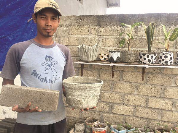 KREATIF: Ahmad Redam Sunalis menunjukkan pot dari sampah popok bayi dan batako hasil kreasinya di TPST Desa Jatinom, Kecamatan Kanigoro, beberapa waktu lalu.