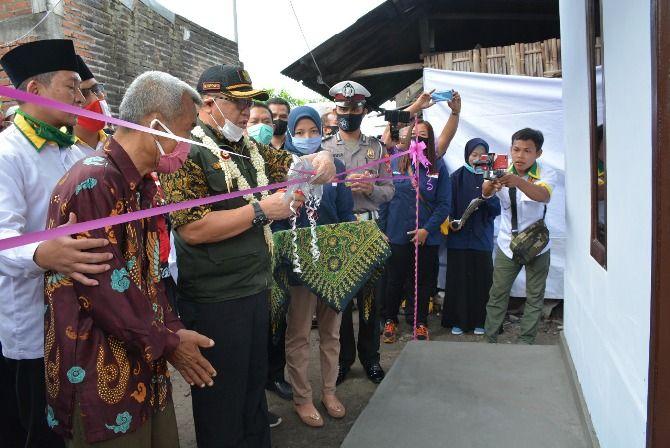 LAYAK HUNI : Bupati Tulungagung Maryoto Birowo menggunting pita sebagai simbol penyerahan rumah layak huni ke Kadis, warga Kelurahan Bago, Kecamatan Tulungagung