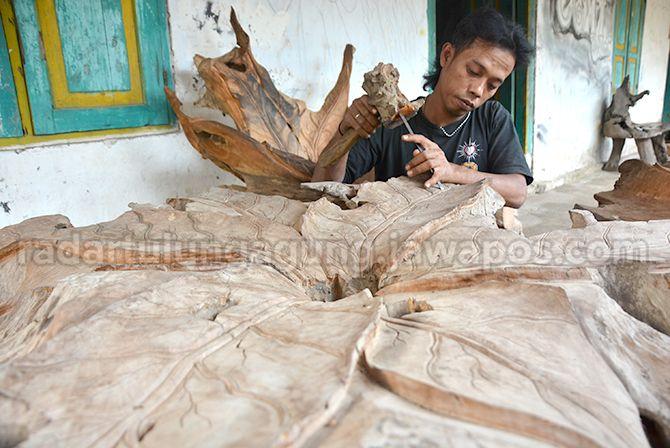 PRODUKTIF: Sigit Prasetyo memanfaatkan waktu longgar untuk mengerjakan ukiran berbahan akar kayu.