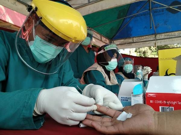 AYO PATUHI PROTOKOL KESEHATAN :Petugas kesehatan mengambil sampel darah untuk melakukan uji RDT kepada salah satu pengunjung di pasar Hewan Boyolangu beberapa waktu lalu.