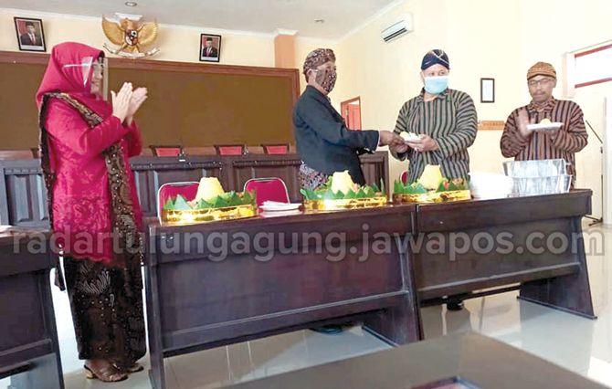 TETAP MERIAH : Plt Kepala Dispendikpora Kabupaten Tulungagung, Hariyo Dewanto Wicaksono menyerahkan potongan tumpeng kepada Kabid Pembinaan SMP, Saifudin Zuhri.