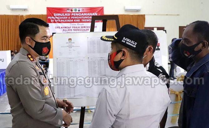 RAMAH : Kapolres Trenggalek AKBP Donny Satria Sembiring saat berbincang dengan undangan lain di sela – sela acara simulasi pengamanan pemungutan dan penghitungan suara di tingkat TPS.