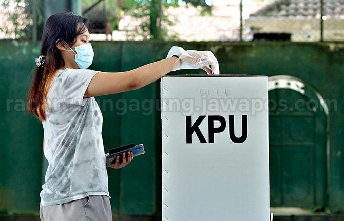 BERPARTISIPASI: Seorang pemilih yang hendak memasukkan surat suara ke kotak suara pada 9 Desember lalu.