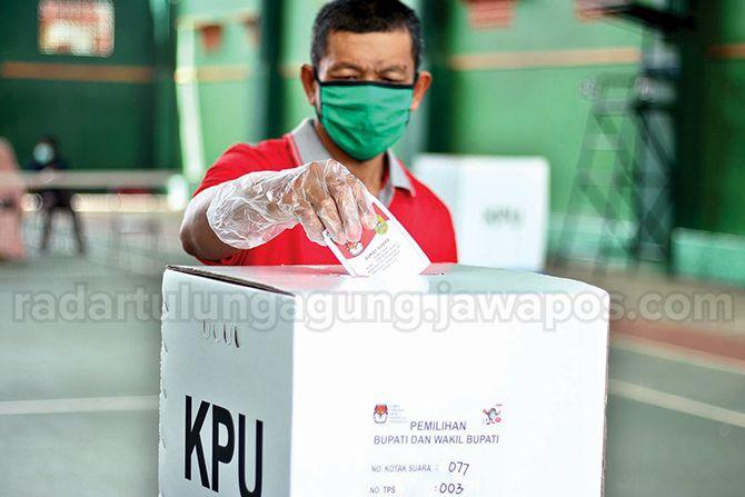 TEGAS: Salah satu pemilih yang sedang memasukkan surat suara ke kotak suara.