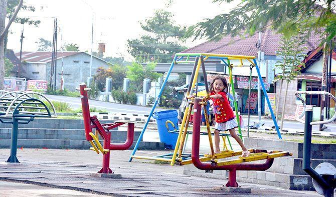 DALAM PENGAWASAN: Seorang anak bermain di area Taman Alun-Alun Kanigoro, kemarin (4/5)