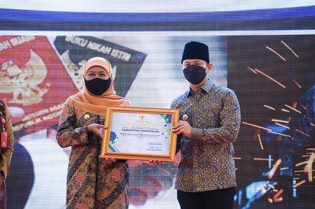 SUKSES : Gubernur Jawa Timur Khofifah Indar Parawansa saat menyerahkan penghargaan kepada Bupati Trenggalek Mochamad Nur Arifin.