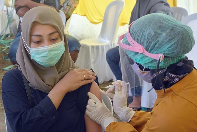 PERLINDUNGAN: Seorang nakes memvaksinasi warga beberapa hari lalu. Kini nakes juga mendapat vaksinasi tahap III.